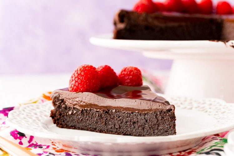Slice of chocolate cake topped with raspberries on a white plate.