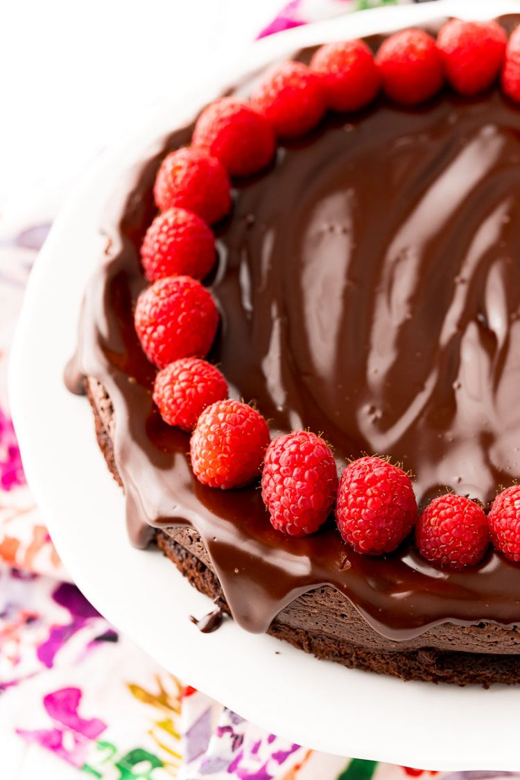 Close up photo of a chocolate cake topped with ganache and raspberries on a white cake stand.