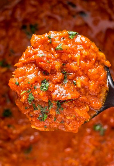 Close up photo of a ladle of marinara sauce.