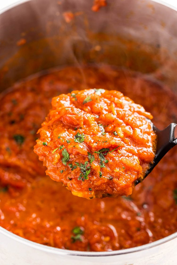 A ladle lifting a scoop of homemade marinara sauce out of a pot.