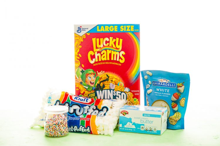 Photo of ingredients to make lucky charms treats including sprinkles, marshmallows, lucky charms cereal, butter, and white chocolate.