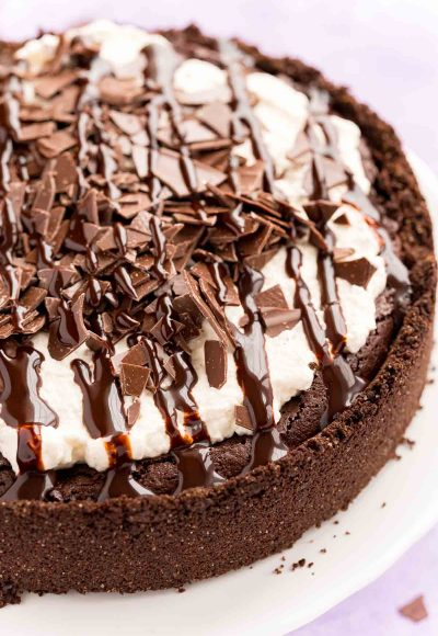 Close up photo of a Mississippi Mud Pie on a white cake stand with chocolate pieces and chocolate drizzle on top.