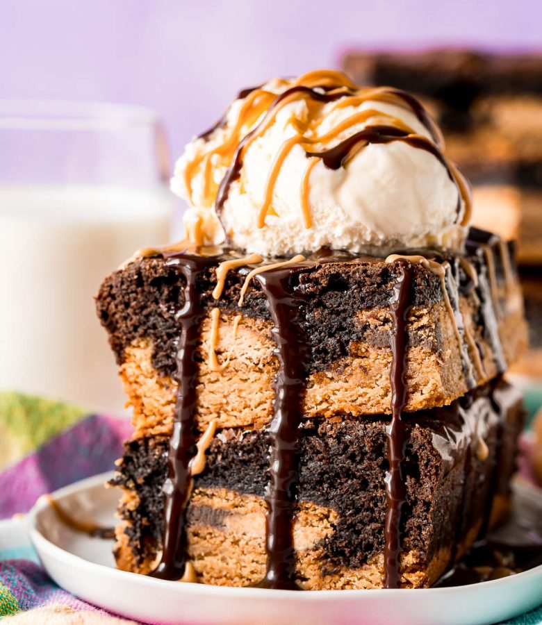 Two slutty brownies stacked on top of each other and topped with a scoop of vanilla ice cream and drizzled with peanut butter and hot fudge sauce.