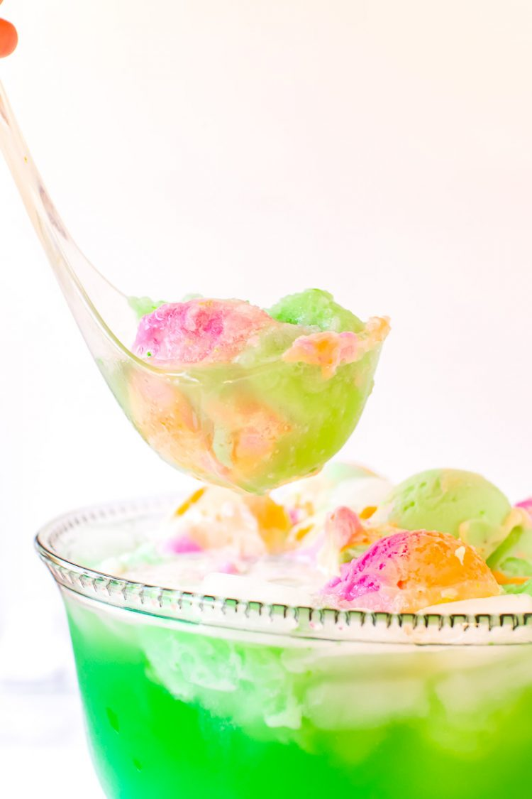 A ladle scooping green punch out of a bowl.