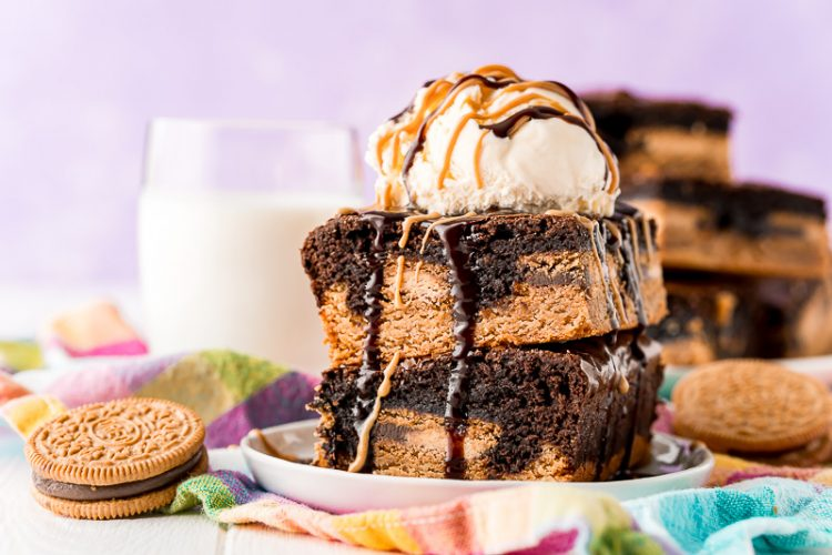 Close up photo of brownies stacked on a white plate with more brownies in the background with a glass of milk.