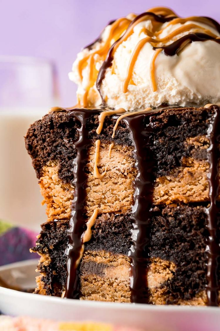 Close up photo of two brownies stacked on top of each other topped with ice cream and drizzled with chocolate and peanut butter.