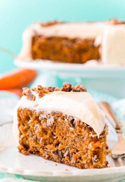Slice of carrot cake on a white plate with a fork. Full cake on a cake stand in the background.