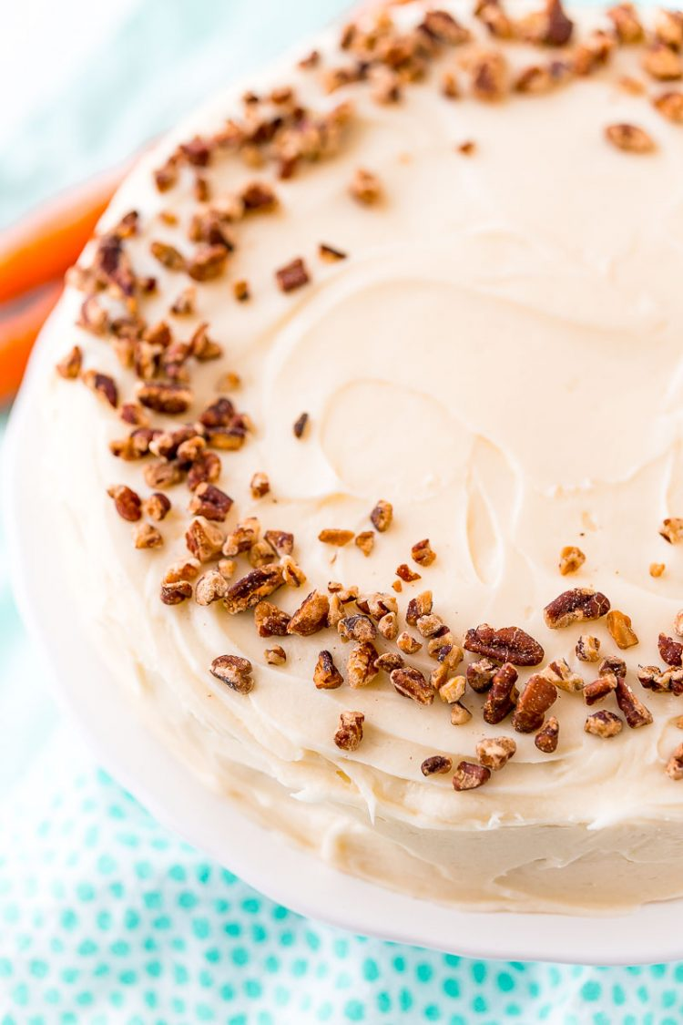 Whole carrot cake topped with chopped pecans.