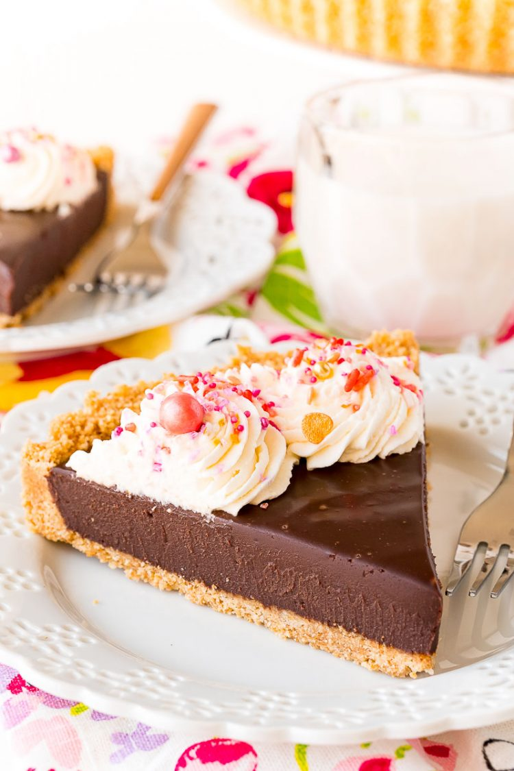 Slice of chocolate tart topped with whipped cream and sprinkles sitting on a white plate.
