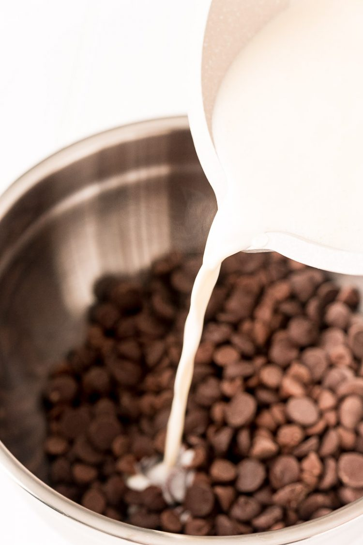 Warm cream being poured into a bowl with chocolate chips.