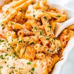 Baked ziti in a white casserole dish with a white serving spoon.