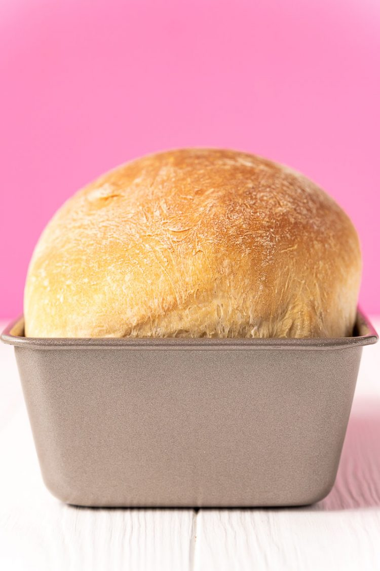 baked loaf of bread in a bread pan on a white table.