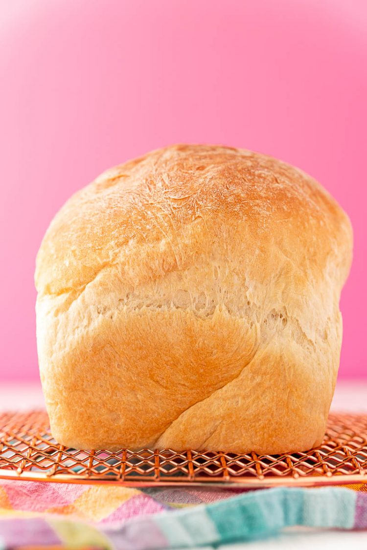 A loaf of white bread sitting on a cooling rack on to colorful napkin.