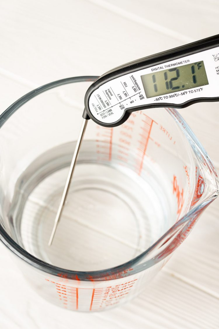 Digital thermometer in a measuring cup of water.