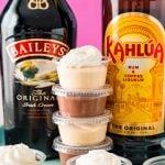 Stack of pudding shots between a bottle of Baileys and a bottle of Kahlua.