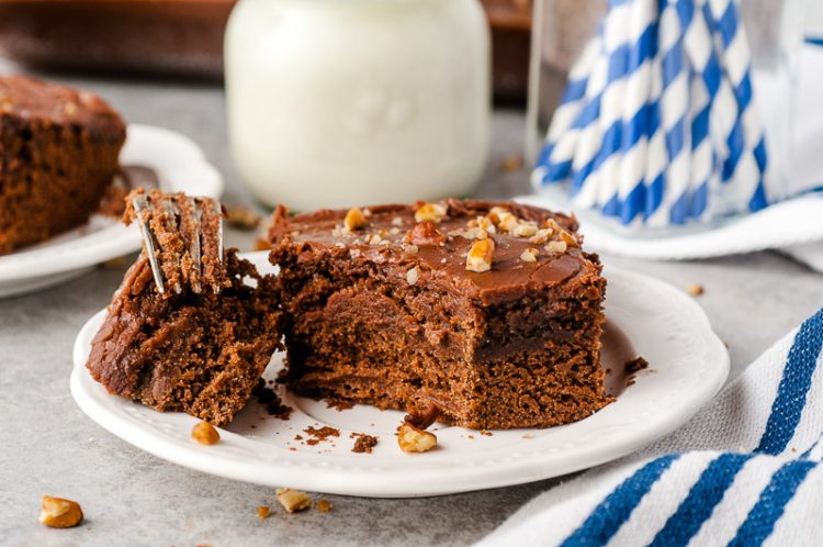 Slice of buttermilk chocolate cake with a bite taken out of it.
