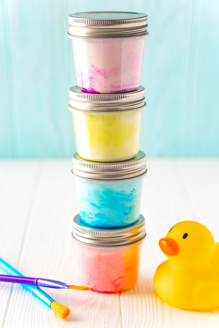 Small jars of paint stacked on top of each other with a rubber ducky and paint brushes sitting next to them on a white table.