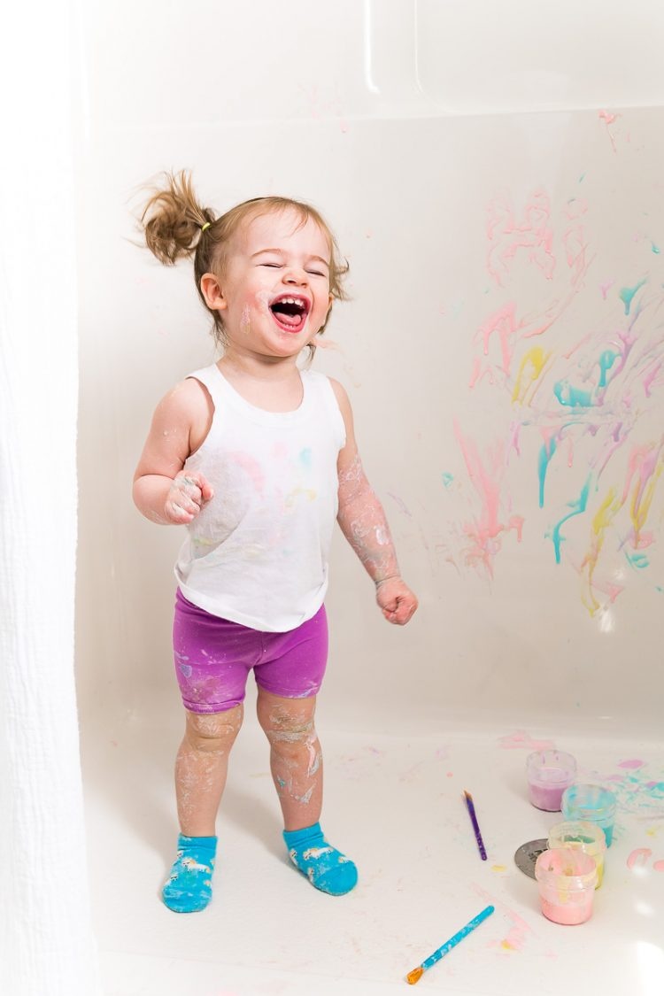 Toddler girl painting with bath paints.
