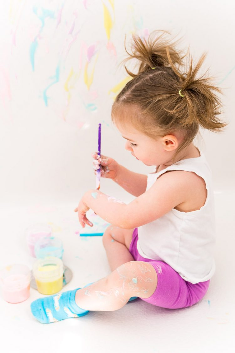 Toddler girl painting with bath paint.