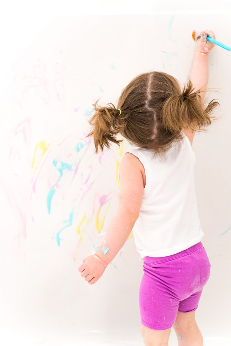Toddler girl painting the tub with bath paint.