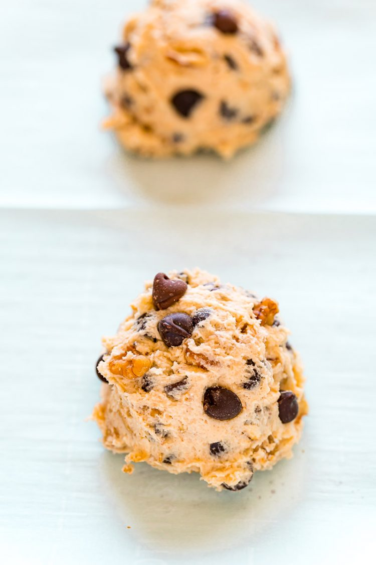 Cookie dough scoops on parchment paper on a baking sheet.