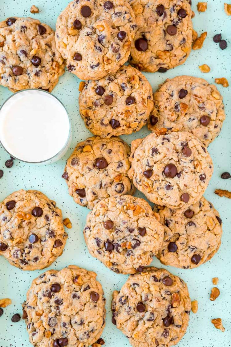 Chocolate chip walnut cookies on a baking sheet with a glass of milk.