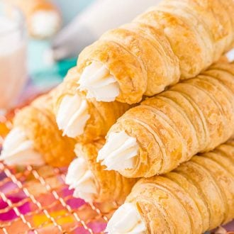 Six cream horns stacked on top of each other on a wire rack.