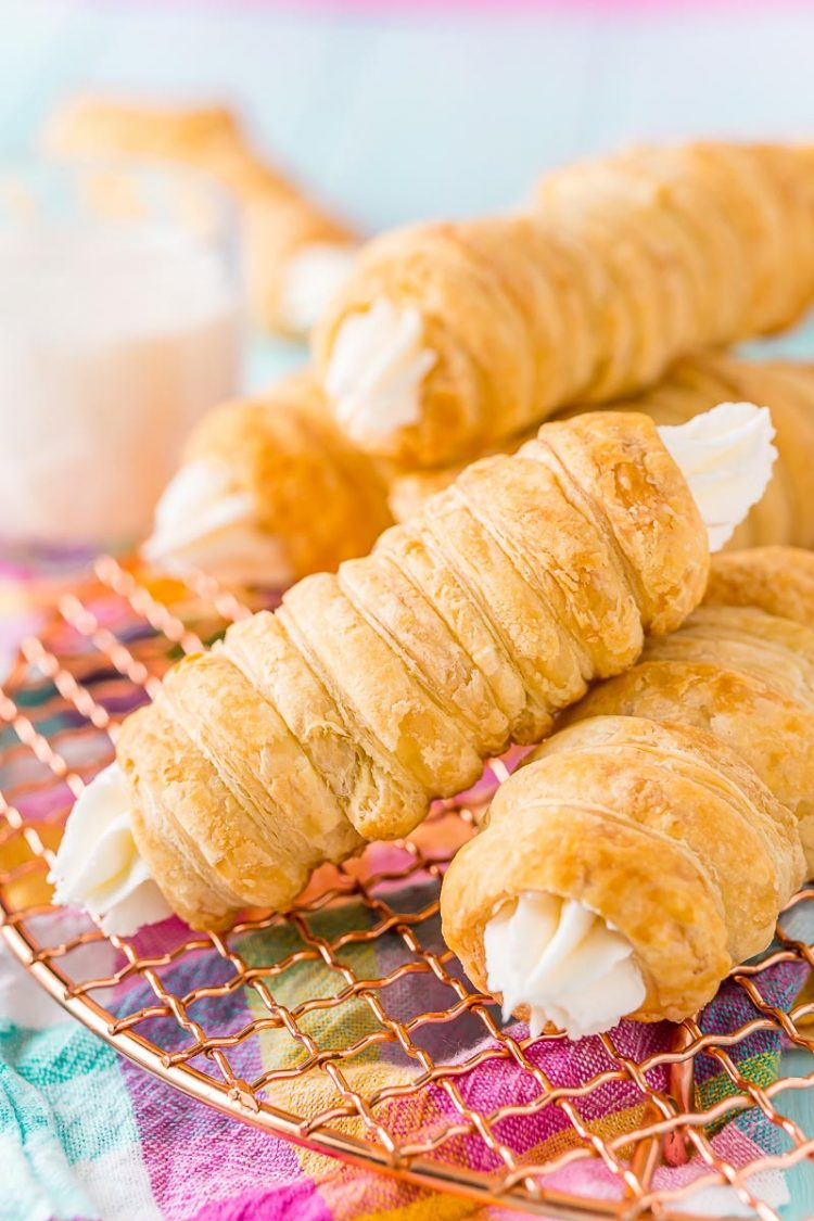 Cream horns stacked on top of each other on a wire rack with a glass of milk in the background.