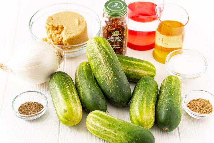 Ingredients to make bread and butter pickles on a white table.