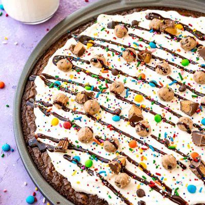 Close up photo of brownie dessert pizza in a pan on a purple surface with candy scattered around.