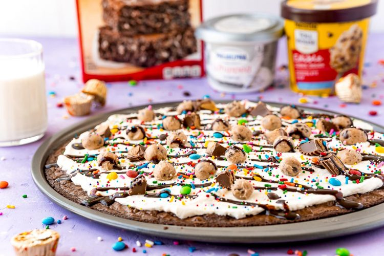 Brownie pizza on a pan with ingredients and a glass of milk in the background.