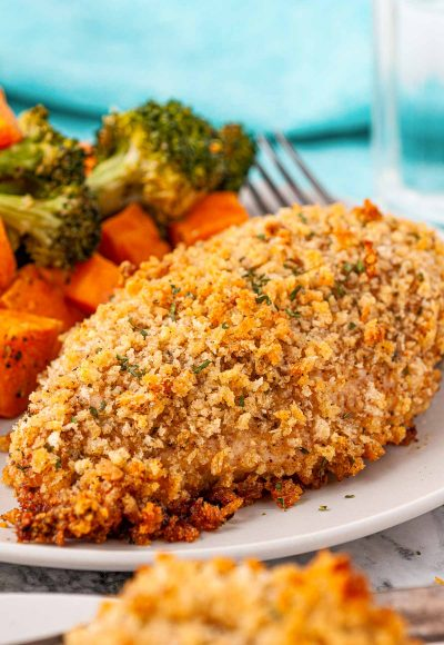 Breaded chicken breast on a white plate served with vegetables.