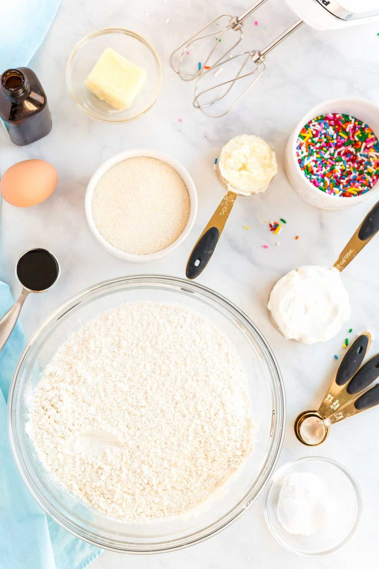 Ingredients to make sugar cookies on a white marble countertop.