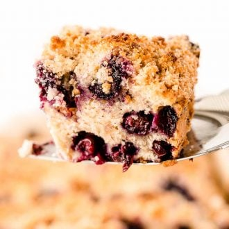 A spatula lifting a slice of blueberry buckle out of the pan.