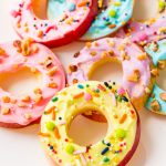 Apple donut slices topped with cream cheese frosting and sprinkles on a white plate.