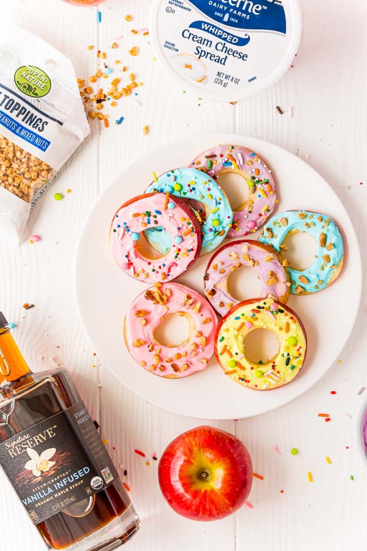Apple donut slices on a white plate with the ingredients to make them scattered around.