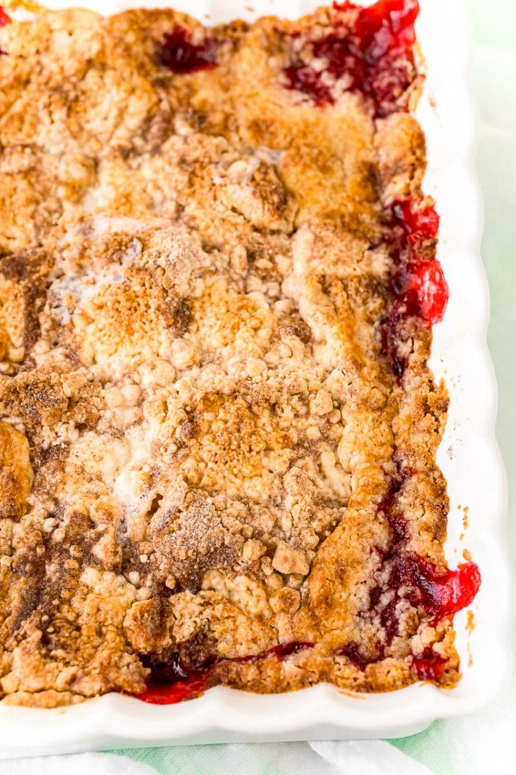 Close up photo of strawberry dump cake cobbler in a white baking dish.