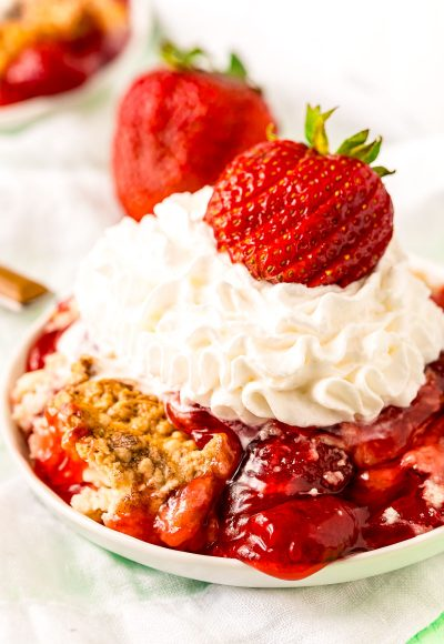 Strawberry dump cake on a white plate topped with whipped cream and a fresh strawberry.