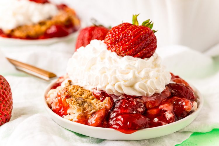 Close up photo of strawberry cobbler on a white plate topped with whipped cream and fresh strawberry.