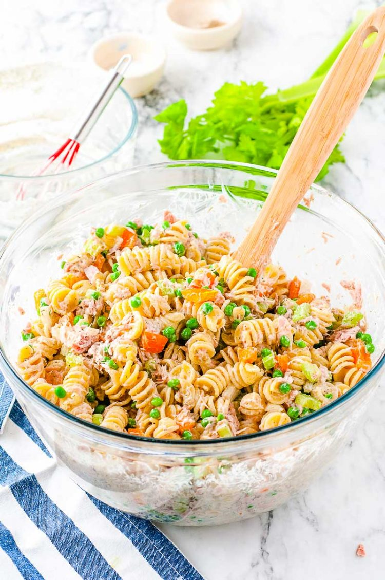 Tuna pasta salad in a glass mixing bowl with a wooden spoon.