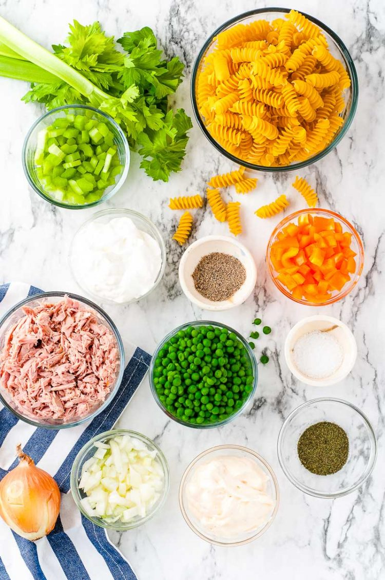Overhead photo of ingredients prepped to make a pasta salad on a marble surface.