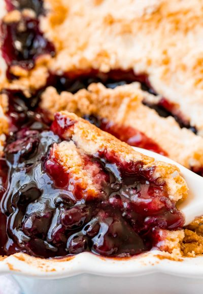 blueberry cobbler in a baking dish with a spoon scooping some out.