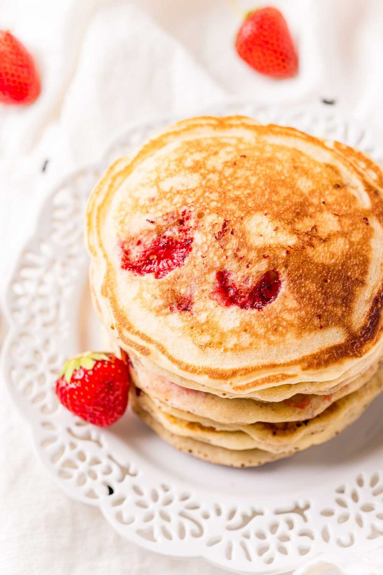 A stack of strawberry pancakes on a white plate.