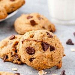 Chocolate Chip cookies on a counter with chocolate chips scattered around and a glass of milk in the background.