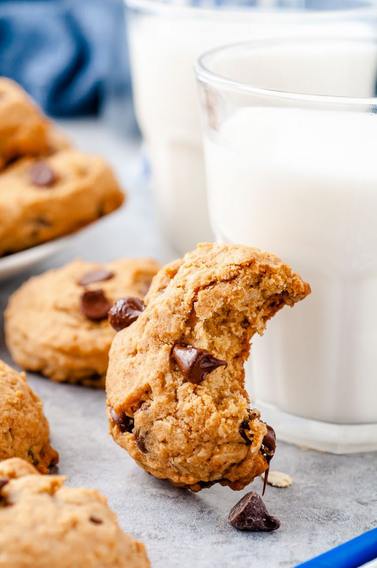 Oatmeal chocolate chip cookie with a bite taken out of it leaning against a glass of milk.