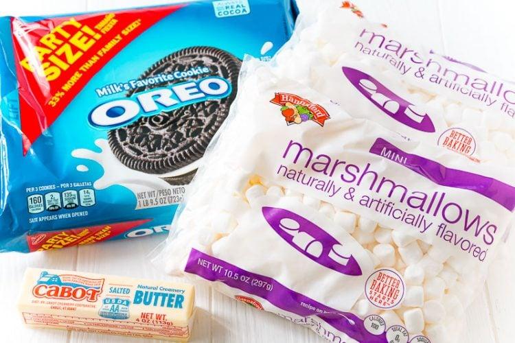 ingredients to make marshmallow oreo treats on a white table.