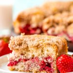 A slice of strawberry coffee cake on a small white plate with a strawberry sitting next to it. More coffee cake in the background.