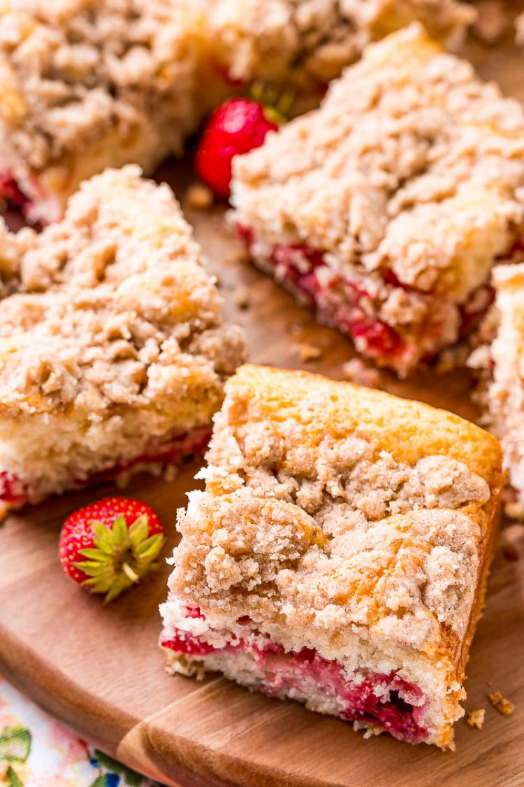 Slices of coffee cake on a wooden cutting board with strawberries scattered around.