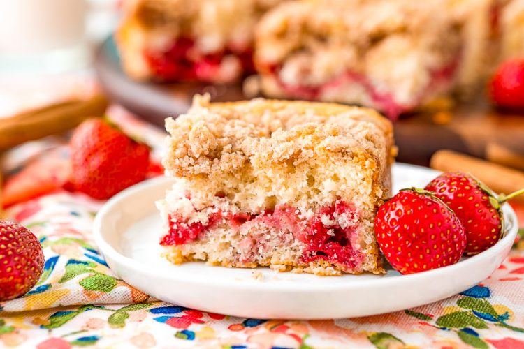 Strawberry coffee cake slice sitting on a white dessert plate with more strawberries scattered around.