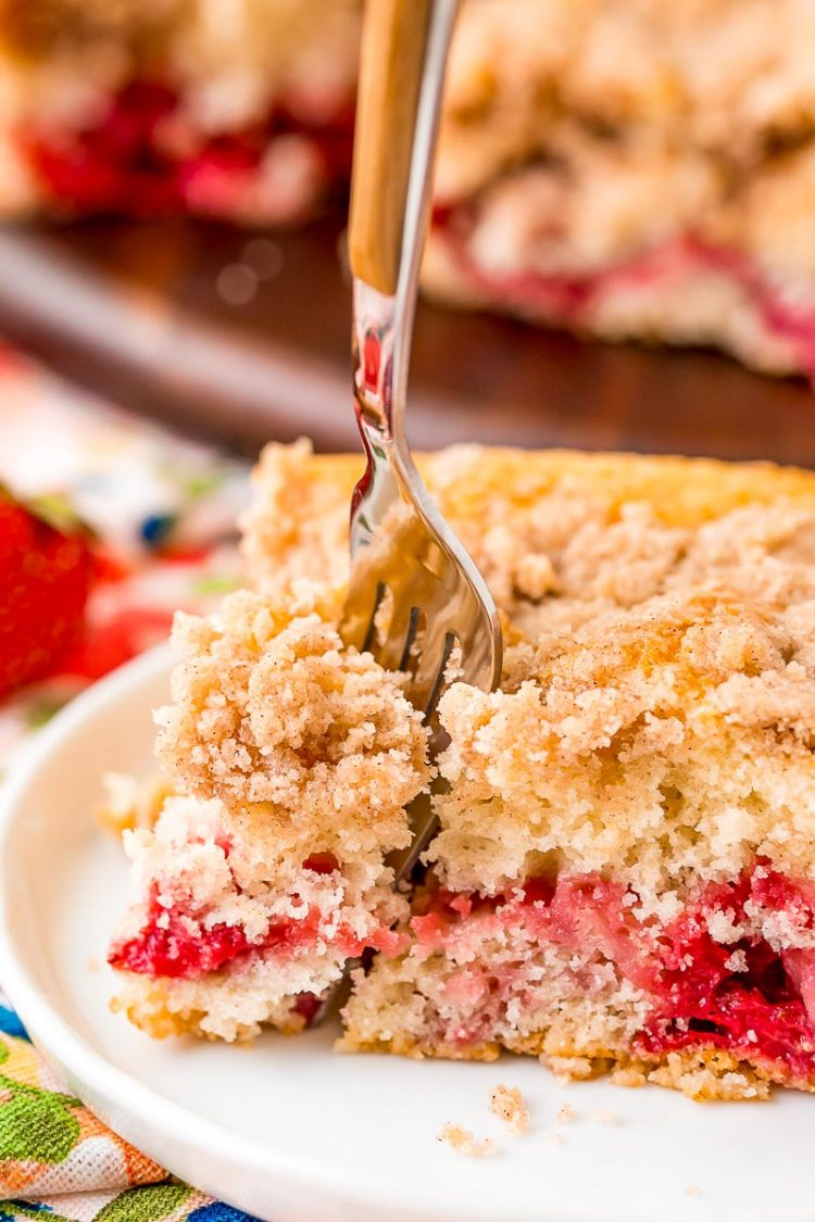 A fork taking a bite out of a strawberry coffee cake slice on a white plate.